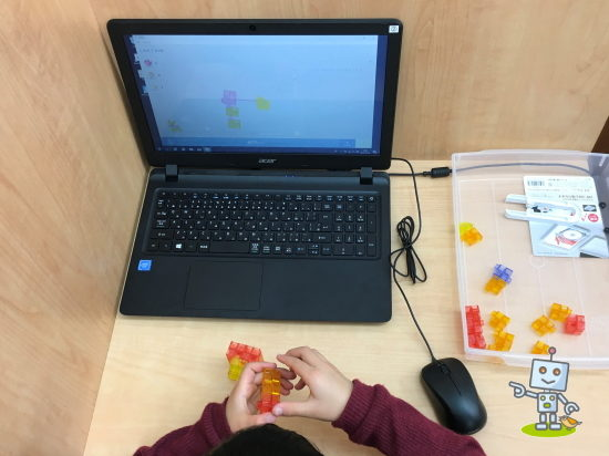 アクシスaxisのロボットにプログラミングをする小学生