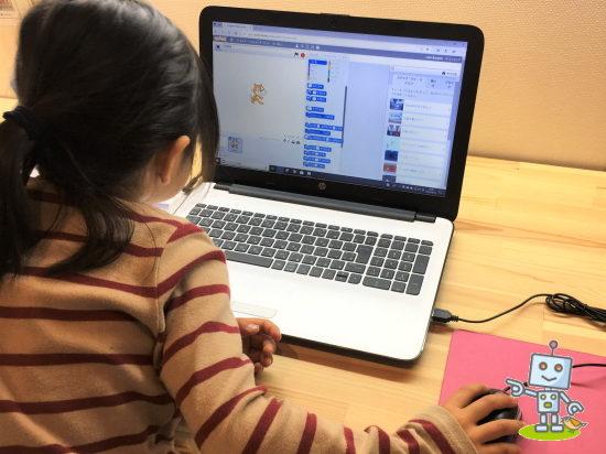 パソコンでプログラムを打ち込む小学生
