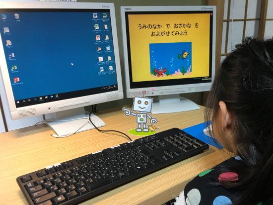 2台のパソコンで学習する小学生女子