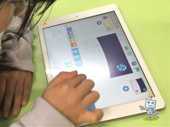 タブレットでプログラミングする小学生
