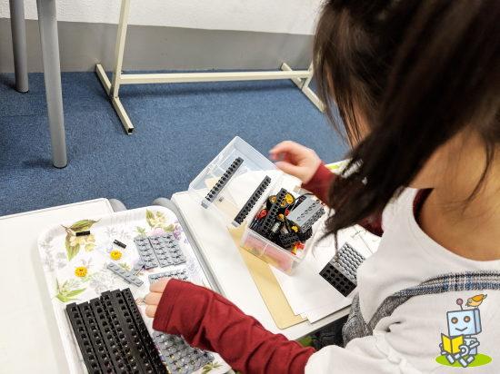 北区ロボット教室でテキストを読んで組み立て作業をする女の子