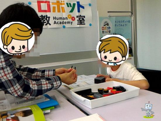 ロボットプログラミング教室で先生に指導を受ける小学生